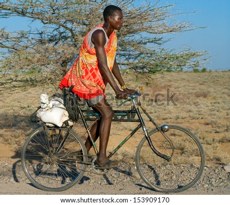 NORTHERN KENYA-JAN 05: Turkana man  rides a bicycle Jan 5, 2013. The Turkana people are the second largest of the pastoral people of Kenya. They occupy  an area of about 67,000 square kilometers. - stock photo