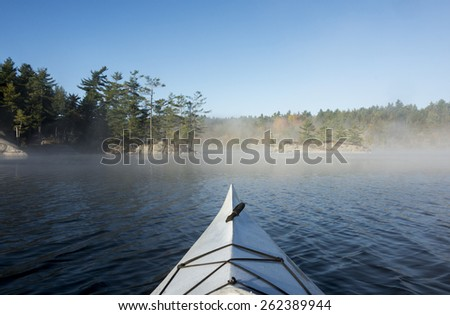 Northern Lake in October with the fog breaking to a blue sky and a sunny day