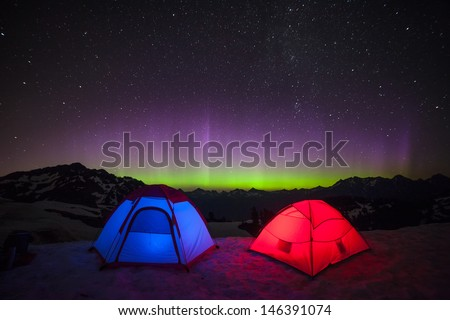 Northern Lights and Glowing Tents - stock photo