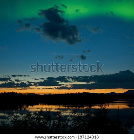 Northern lights  Aurora borealis  at midnight in summer over northern horizon of Lake Laberge  Yukon Territory  Canada  midnight sun just below - stock photo