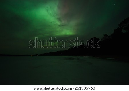 Northern lights (Aurora borealis) over frozen lake - stock photo