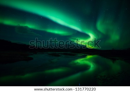 Northern lights (Aurora borealis) reflection across a lake in Iceland - stock photo