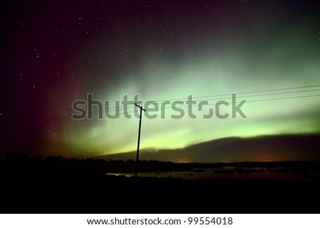 Northern Lights behind a power pole - stock photo