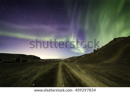 Northern lights blazing over a desert gravel road leading into the distance - stock photo
