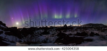 Northern Lights bursting above an Arctic rocky landscape - stock photo