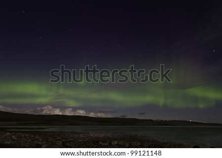 Northern lights dance over Tongue in Scotland. - stock photo