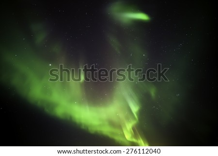 Northern lights filling the night sky over iceland in winter - stock photo