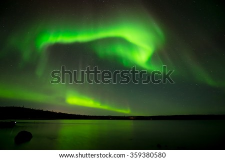 Northern Lights in Starry Sky - Bright northern lights rolling over the starry night sky over a lake.  - stock photo
