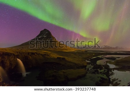 Northern lights moving over Kirkjufell volcano with fully of stars in sky, Iceland natural landscape - stock photo