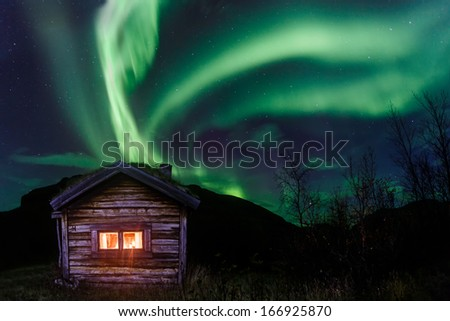 Northern lights over an old Cabin - stock photo