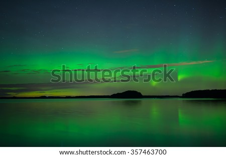 Northern lights over calm lake in Sweden (Aurora borealis) - stock photo