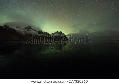 Northern lights over frozen lake Vestrahorn in Iceland  - stock photo