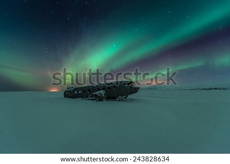 northern lights over plane wreck on the black beach in Vik, Iceland - stock photo