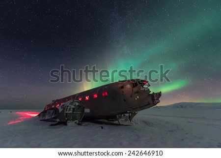 northern lights over plane wreck on the wreck beach in Vik, Iceland  - stock photo