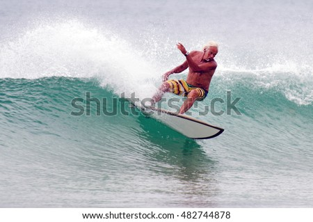 NORTHLAND, NZL - JAN 20 2013:Mature old man wave surfing.Some surfers practice surfing as a recreational activity while others make it the center of their lives as a spiritual experience or a religion