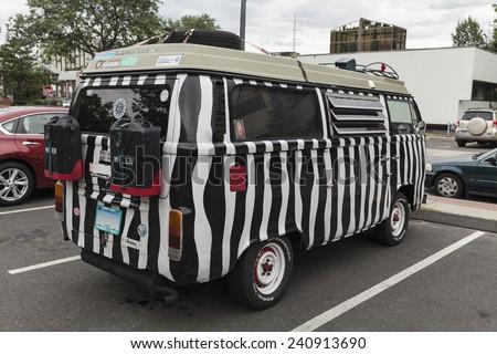 Norwalk, CT - August 15, 2014: Iconic Volkswagen minivan painted as zebra with hippies stickers - stock photo