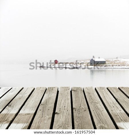 Norway Cottage on winter coast with wooden platform dock - stock photo