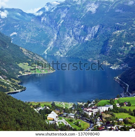 Norway cruise: mountains and village in Geiranger fjord. - stock photo