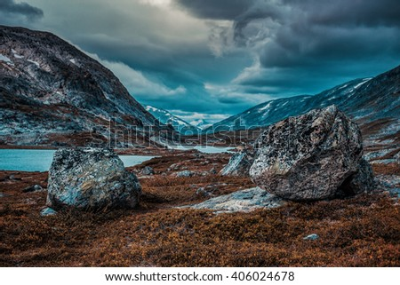 Norway high mountains landscape with small lake. Autumn film style dramatic colors. - stock photo
