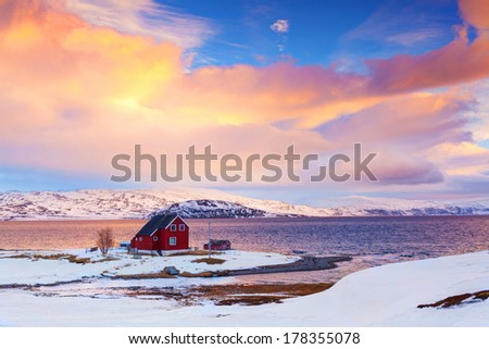 Norway in winter: mountains with red house and the ocean at sunset. - stock photo