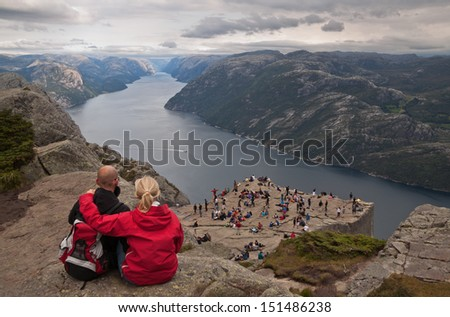 NORWAY - JUNE 2, 2009: unidentified group of tourists enjoy breathtaking views from Preikestolen  rock. Preikestolen rock cliff is one of the most popular tourist attractions in Norway.  - stock photo