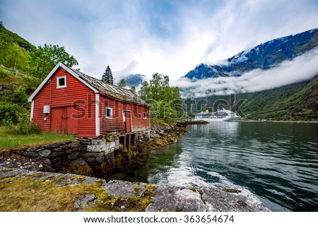 Norway landscape, the house on the shore of the fjord in the background berth cruise ship. - stock photo