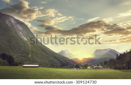 Norway scenic mountain landscape. Norwegian village at sunset (sunrise). Mountains valley with clouds and sunshine.  - stock photo