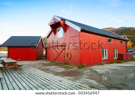 Norway, Vingvagen village. Red wooden fishing barns stand on the sea coast