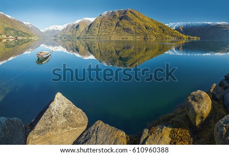 Norwegian autumn landscape fjord with reflection of snow-capped mountains in clear water and fishing boat