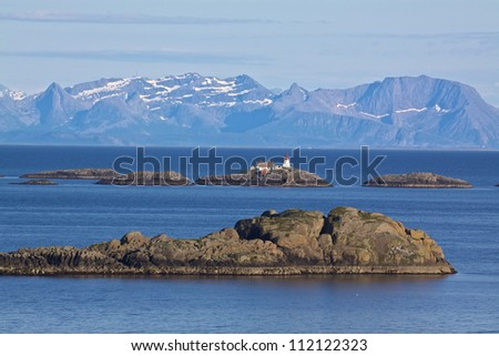 Norwegian coast with tiny rocky islets, picturesque lighthouse and high mountains in the background