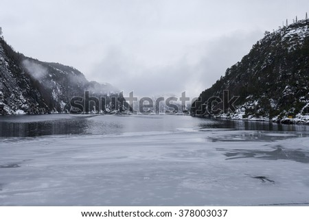 Norwegian fjords in winter time with snow on the mountains and ice on the water.
