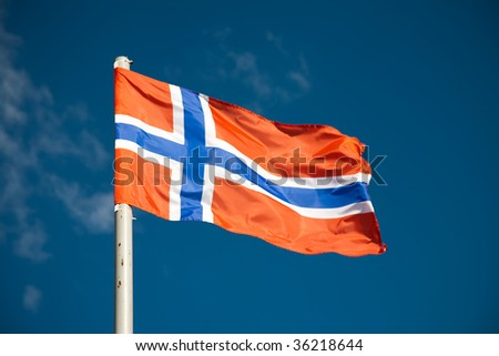 Norwegian flag against blue sky - stock photo