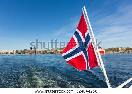 Norwegian flag waving on poop of a boat in the Oslo fjord. On background there are the wake of the ship into the sea and the city of Oslo.