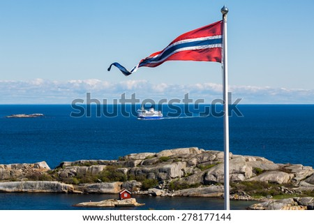 Norwegian flag with a small red cabin and an unmarked ferry in the background - stock photo
