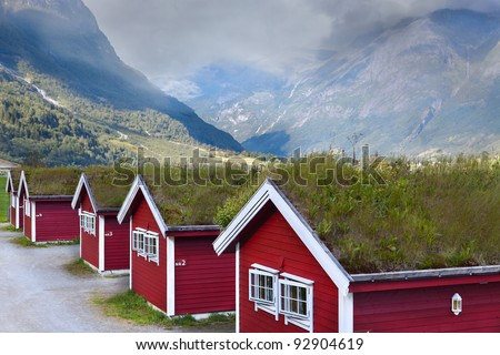 Norwegian houses in the mountains with green roofs - stock photo