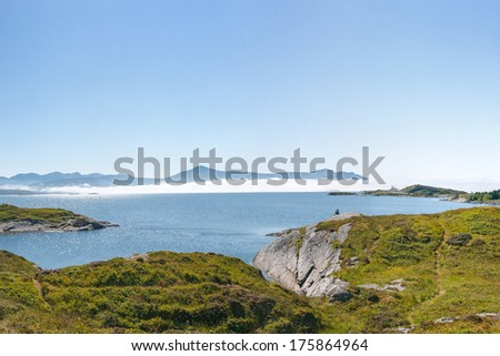 Norwegian landscape: view at Kvernesfjorden with clouds on the water and remote Atlantic Road. Man enjoying view. - stock photo