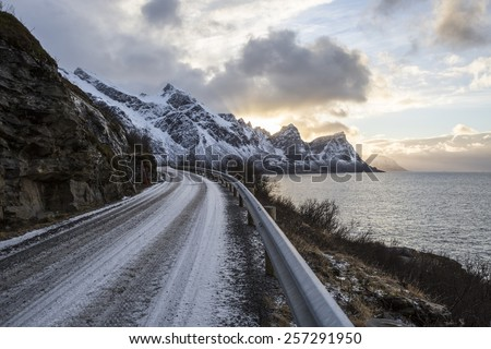 Norwegian landscape with a tiny road along the seaside in a fjord in the winter, Nordland, Norway - stock photo