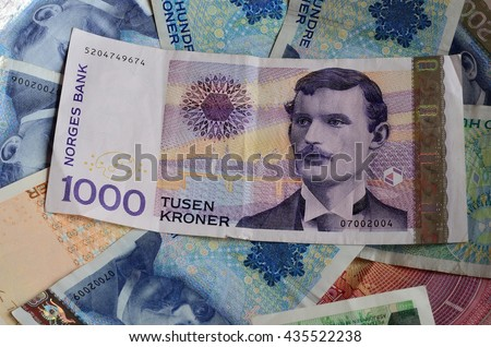 norwegian one thousand crown paper money bill resting on top of two, one and five hundred bills - stock photo