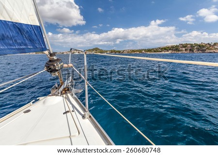 Nose boat with a sail on the background of the shore. Nose boat with a sail and an anchor on a background of the coast on a sunny day. Mallorca, Spain - stock photo