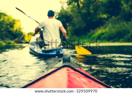 nose of canoe floating behind rower on a river - stock photo