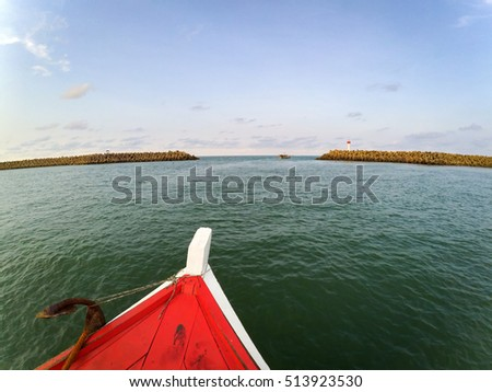 nose of fiber boat sailing to the island.cloudy sky background and splashing water
