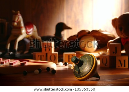 Nostalgic antique wooden spinning top play time toy and traditional collection of old wood children toys with baseball glove and teddy bear with vintage alphabet blocks and marbles in an attic - stock photo