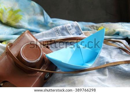 nostalgic background with old camera and blue paper boat/retro nostalgia memories - stock photo
