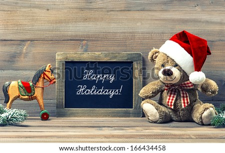 nostalgic christmas decoration with antique toys teddy bear and wooden rocking horse. vintage style toned picture. blackboard with sample text Happy Holidays! - stock photo
