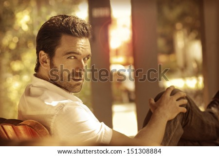 Nostalgic fashion stylized portrait of a great looking masculine man relaxing on a front porch with legs up turning toward viewer - stock photo