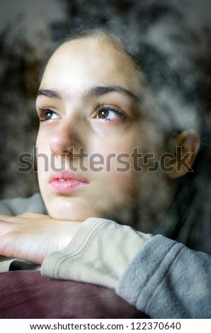 nostalgic girl looking through a window with winter trees reflected in the glass - stock photo