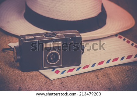 Nostalgic travel explorer concept photo, old film camera, hat and airmail letter on canvas - stock photo