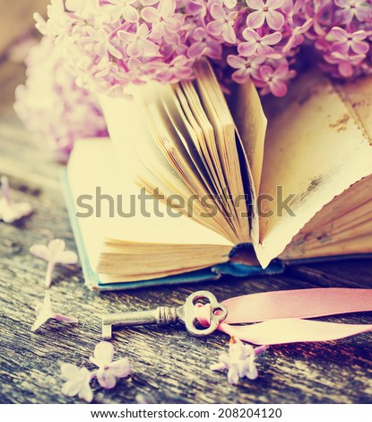 Nostalgic vintage background/ Vintage book,Photos of Memories and key with lilac flower - stock photo