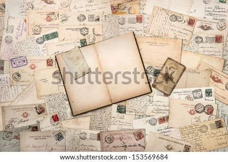 nostalgic vintage background with old handwritten postcards and open empty book - stock photo