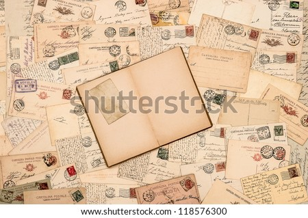 nostalgic vintage background with old handwritten postcards and open empty book page - stock photo